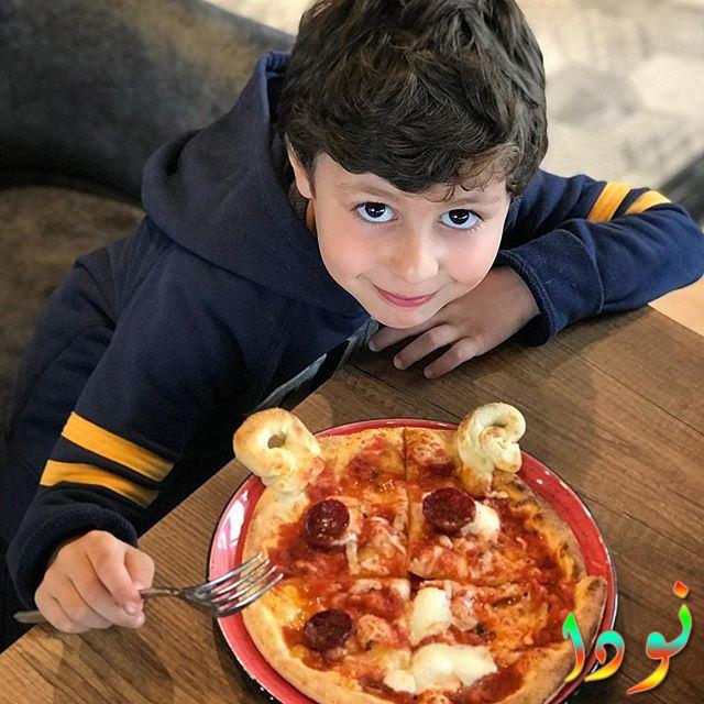 الفنان الصغير دمير بيرينجي يأكل البيتزا