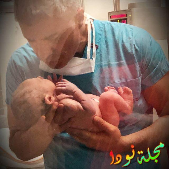 صورة جميلة لأوزجان دينيز وهو يحمل ابنه بعد ولادته مباشرتاً